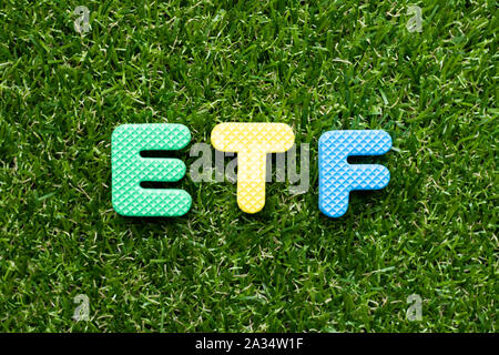 Toy foam letter in word ETF (abbreviation of Exchange Traded Fund) on green grass background - Stock Photo