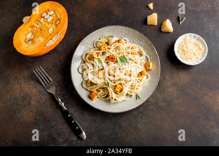 Pumpkin Pasta. Homemade spaghetti pasta with roasted pumpkin, cream, grated parmesan and sage leaves. Seasonal healthy vegetarian food. Top view, copy - Stock Photo