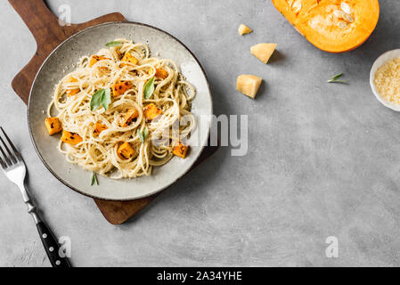 Pumpkin Pasta on concrete background, top view, copy space. Seasonal vegetarian spaghetti pasta with roasted pumpkin, cream, grated parmesan and sage - Stock Photo