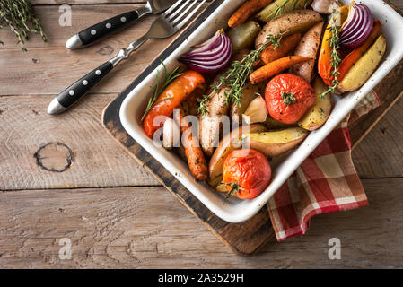 Oven roasted vegetables with spices and herbs in baking dish on wooden table. Vegetarian vegan  healthy organic autumn meal - baked vegetables. - Stock Photo