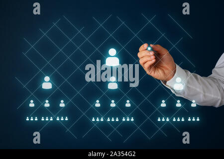 Network marketing concept with businessman drawing people icons and pyramid scheme on virtual interface with a glowing stylus pen. - Stock Photo