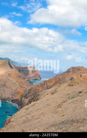 Volcanic cliffs in Ponta de Sao Lourenco, Madeira Island, Portugal. The easternmost point of the island of Madeira, volcanic landscape by the Atlantic ocean. Hikers on the trail. Vertical photography. - Stock Photo