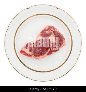 Raw rib-eye steak on plate, isolated on white background - Stock Photo