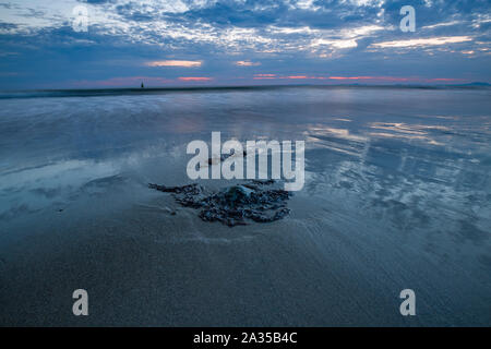 Colorful twilight sky over sandy shore in Barmouth, UK. Long exposure - Stock Photo