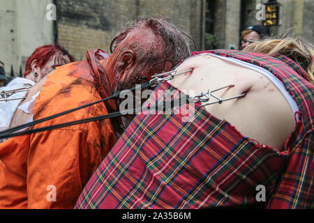 London, UK. 05th Oct 2019. While most of this years participants to Zombie Day In London ,choose to dress and use make up to look as scary as possible ,this group choose to go for the shock  impact by allowing themselves to be pulled by hooks attached to their back trough the streets of London .Paul Quezada-Neiman/Alamy live News - Stock Photo