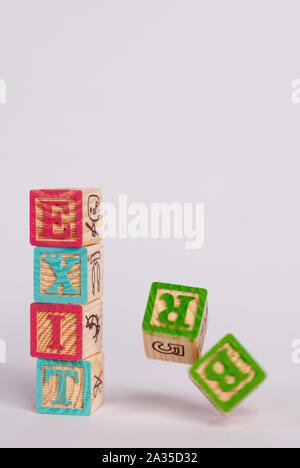 The word 'Brexit' in coloured wooden blocks, with a light background and shadows. The 'B' and the ''R' of Brexit are falling. Copy space available. - Stock Photo