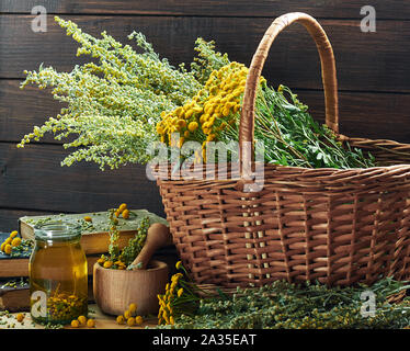 Helminthic herbs: absinth and tansy; fresh herbs in the wicker basket and wooden mortar, on old books, healing infusion is nearby, closeup, copy space - Stock Photo