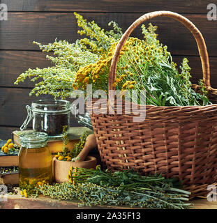 Herbal helminthic triad: absinth, tansy and cloves; fresh herbs in the wicker basket and wooden mortar, on old books,  healing infusion is nearby, clo - Stock Photo