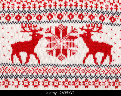 Close-up shot of red knitted elks and snowflake Scandinavian style ornament cristmas sweater background