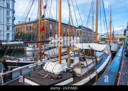 Copenhagen, Denmark - May 04, 2019: Colourful facades and restaurants on Nyhavn embankment and old ships along the Nyhavn Canal in Copenhagen, Denmark - Stock Photo