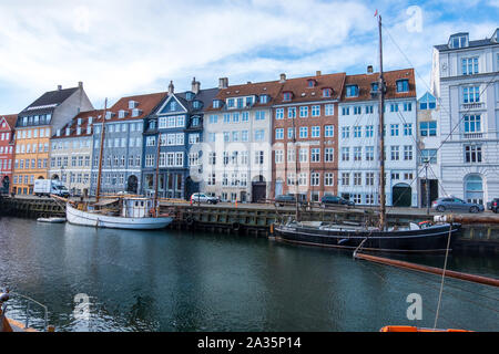 Copenhagen, Denmark - May 04, 2019: Colourful facades and restaurants on Nyhavn embankment and old ships along the Nyhavn Canal in Copenhagen, Denmark