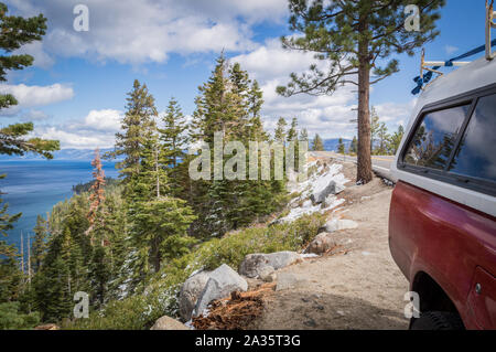 A red four by four truck parked on the side of an overlook of Emerald Bay in Lake Tahoe, California on a sunny day in early winter with snow and gree. - Stock Photo