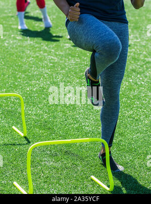 A high school female athlete performs running drills over mini hurdles while wearing socks but no shoes on a green turf field. - Stock Photo