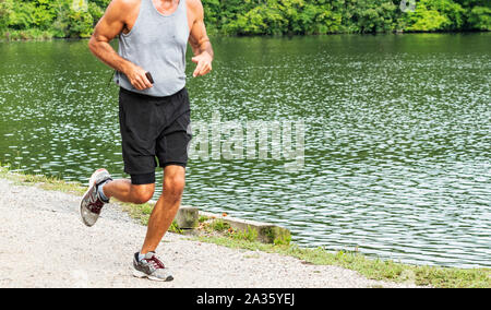 A runner is holding on to their phone while running a race in the woods passing a lake. - Stock Photo