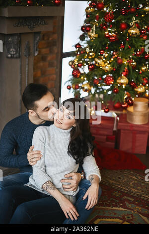 The young happy couple, in warm sweaters. Young handsome man kissing a beautiful girlfriend near the fireplace and Christmas tree in the background - Stock Photo