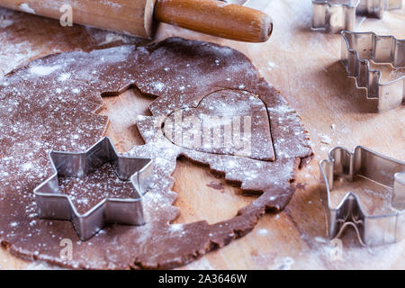 Raw christmas homemade gingerbread dough rolled out with Christmas shapes - Stock Photo