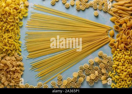 Assorted Italian pasta: Penne rigate, Rotelle, Conchiglie, Cavatappu, Fusilli, Cellentani, Spaghetti, horizontal orientation, top view - Stock Photo