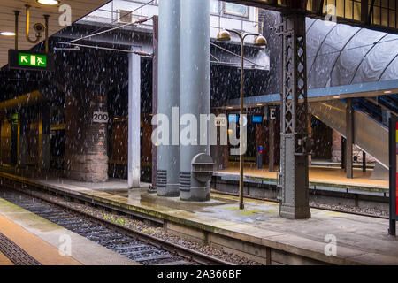 Copenhagen, Denmark - May 04, 2019: Snowflakes falling on platforms of Copenhagen Central Station. It is the main railway station in Copenhagen - Stock Photo