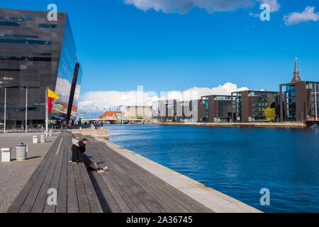 Copenhagen, Denmark - May 04, 2019: People relax on one of the waterfront near the Black Diamond, the Copenhagen Royal Library - Stock Photo