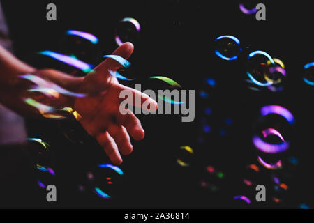 Colorful soap bubbles flying over darck background and human hand tryimg to catch them - Stock Photo