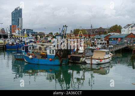 Fishing boats docked in a quay reflecting on calm waters at camber docks in old Portsmouth, Hampshire - Stock Photo