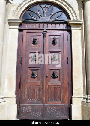 A large double door at the entrance to St. Mary's Basilica adorned by busts. - Stock Photo