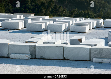 Large rectangular blocks of natural white Carrara marble in the forecourt of an Italian mine ready for use in construction and sculpture - Stock Photo