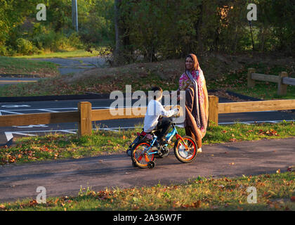 Berlin, CT USA. Sep 2019. South Asian immigrant and son on bicycle enjoying the New England fall season at the park. - Stock Photo