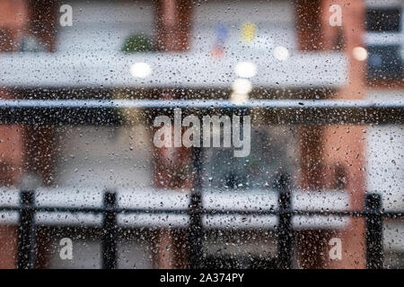 Many raindrops on a window glass on a blurry background - Stock Photo