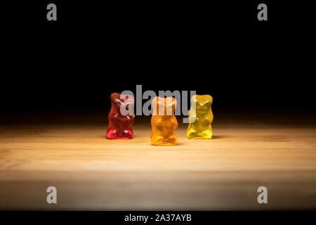 A portrait of three different colored gummi bears, the candy is standing on a wooden plank with lighting that looks like they are on a stage. - Stock Photo