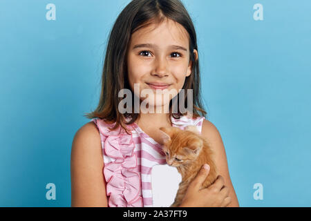 attractive smiling little girl hugging her orange kitten, looking at the camera. close up portrait, leisure, pastime - Stock Photo