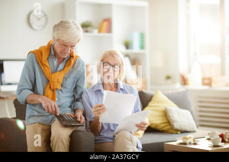 Portrait of modern senior couple calculating finances and budget while preparing tax report at home, copy space - Stock Photo