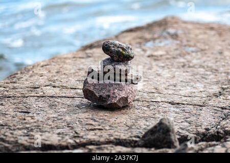 Stones pyramid on sand symbolizing zen, harmony, balance. Sea in the background. - Stock Photo