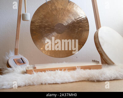 Sound therapy set up with gong, shamanic drum and sansula on a sheep skin - Stock Photo