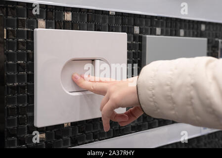Female hand pressing a toilet flush button on the wall. - Stock Photo