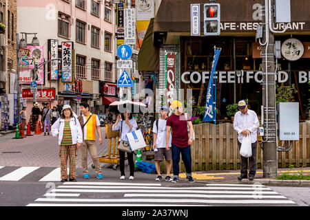 Japanese people ages 20s to 70s waiting at a crosswalk on a red light in Tokyo, Japan - Stock Photo