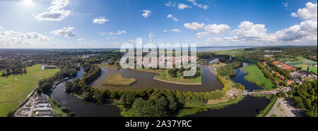 Wide aerial panoramic view on the fortification city Naarden Vesting with its defensive constructions surrounding the village against a blue sky with - Stock Photo