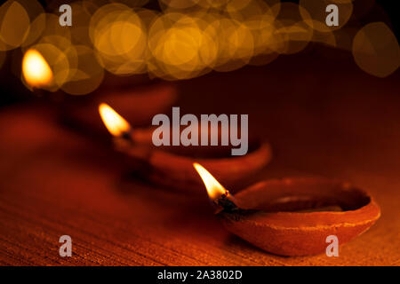 Happy Diwali - Diya oil clay lamps lit during Diwali celebration with light bokeh and copy space. - Stock Photo