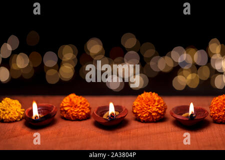 Diwali diya or clay oil lamp burning or glowing on a wooden surface decorated with marigold flowers and bokeh in background and copy space. Concept fo - Stock Photo