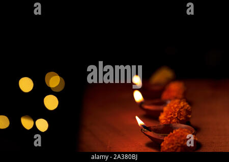 Diwali diya or terracotta oil lamps decorated in a row or line with flowers and copy space isolated in black background and bokeh lights. Concept for - Stock Photo