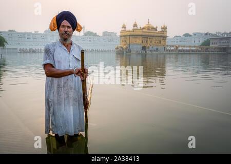 A Sikh cleans the Sarovar (water tank) – around the Golden Temple (Sri Harmandir Sahib),  Amritsar, Punjab, India - Stock Photo