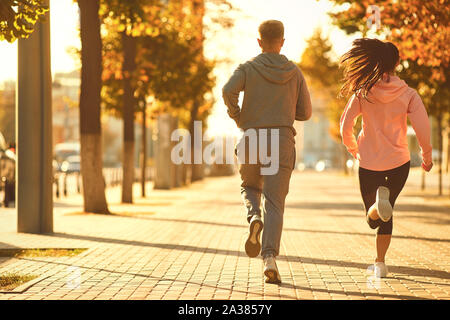 A man and a woman are running along the city street in the morning. - Stock Photo