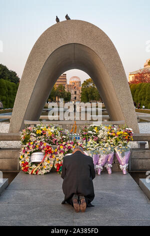 HIROSHIMA, JAPAN – NOVEMBER 23, 2007: The old man praying in front of the Memorial Cenotaph for the A-bomb Victims. Doves of peace are sitting on the - Stock Photo