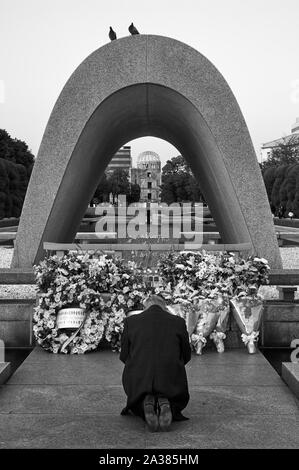 HIROSHIMA, JAPAN – NOVEMBER 23, 2007: Black and white image of old man praying in front of the Memorial Cenotaph for the A-bomb Victims. Doves of peac - Stock Photo