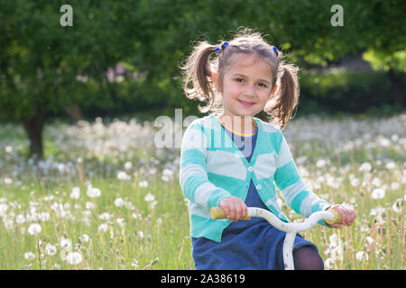 Cheerful little girl on a bike. baby playing on a green meadow. Five-year baby in dandelions - Stock Photo