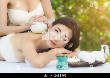 Beautiful young asian woman with back to receive back massage at outdoors in spa salon, day time. - Stock Photo