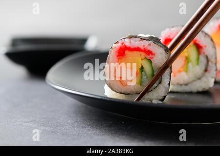 sushi rolls (Vegetable, Inari and  Crab Sticks) with chopsticks, popular Japanese food