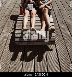 Boy and girl sitting on a sun chair on a terrace, Denmark - Stock Photo