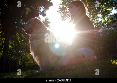 Teenage girl sitting in the park with her dog, Argentina