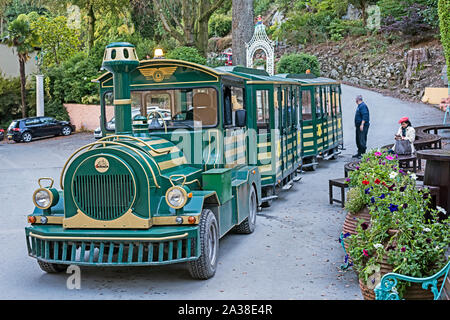 Green tourist shuttle train, waiting passenger  and driver at the Portmeirion village, Wales, UK - Stock Photo